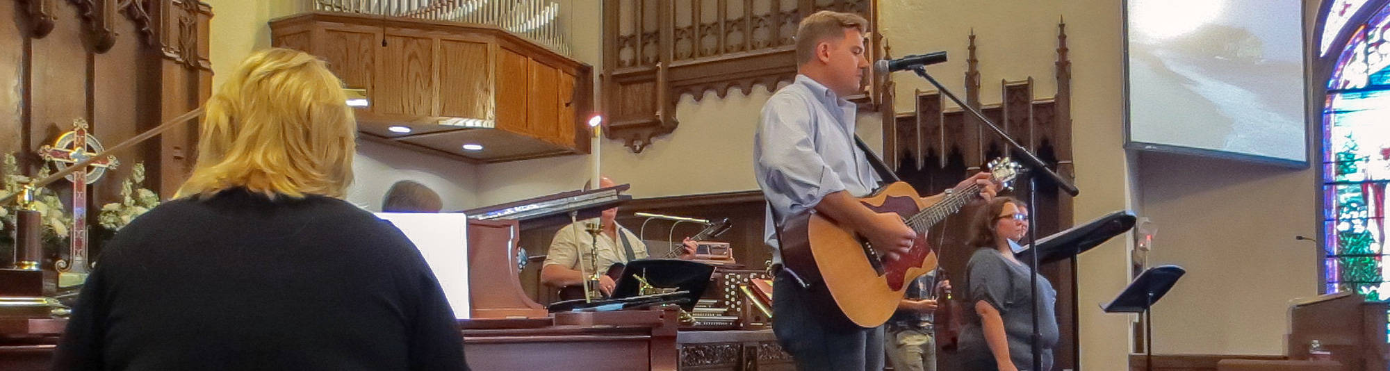 man playing guitar at church